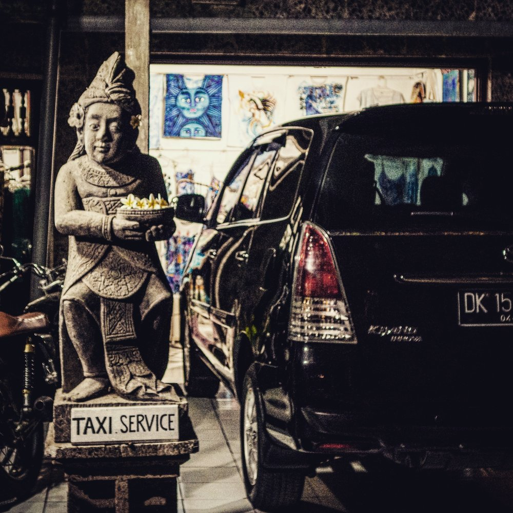 Balinese statue with a taxi service sign